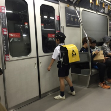 This is a kindergartener riding the Astram (subway) alone. The yellow plastic on his backpace alerts us all that he might need help.